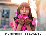 Stock photo beautiful styled girl with flowers blowing petals from her hands sunlight outdoor happy valentines 551202952