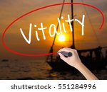 Stock photo woman hand writing vitality with a marker over transparent board isolated on sunset boat 551284996