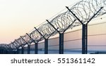 sharp barbed wire on fence at... | Shutterstock . vector #551361142
