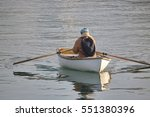A person rows a wooden rowboat...