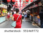 Small photo of Woman tourist walking in chinatown on china travel. Asian girl on Wangfujing food street during Asia summer vacation. Traditional Beijing snacks being sold at chinese chinatown outdoor market.