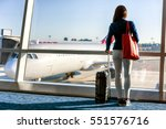 Small photo of Travel tourist standing with luggage watching sunset at airport window. Unrecognizable woman looking at lounge looking at airplanes while waiting at boarding gate before departure. Travel lifestyle.