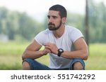 Small photo of Portrait Of A Young Man Sitting on Grass - Handsome Guy Repose in Nature - Outdoors - Outside