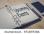 Small photo of Concept Upcoming Events message on notebook with pen and smart phone on wooden table