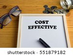 Small photo of COST EFFECTIVE Business concept - Office desk with White board, glasses, pen, and coins