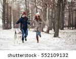 couple walking dog winter | Shutterstock . vector #552109132