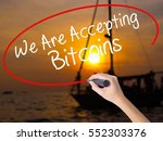 Small photo of Woman Hand Writing We Are Accepting Bitcoins with a marker over transparent board. Isolated on Sunset Boat. Business concept. Stock Photo