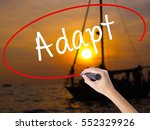Small photo of Woman Hand Writing Adapt with a marker over transparent board. Isolated on Sunset Boat. Business concept. Stock Photo