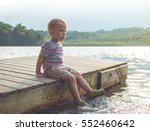 Child Sitting On Dock With Fee...