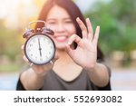 Small photo of Times is OK or Right time with right job concept, Asian women hand show clock times with hand show good alright sign.