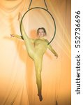 Small photo of Acrobatic artist hanging from the hoop, on stage
