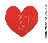 Small photo of Broken red heart with sewed again with white thread