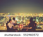 Small photo of Blurred focus of rooftop restaurant with people dinning at night, vintage filtered