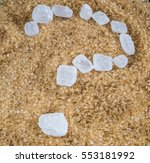 Small photo of The question mark written with crystalline sugar (candy) white into a pile of brown sugar crystal Demerara.