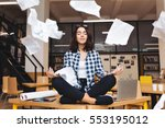 Stock photo young pretty joyful brunette woman meditating on table surround work stuff and flying papers 553195012