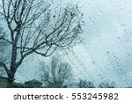 Drops of rain on the windshield, tree branches in the background - stock photo