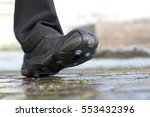 shoe snow spikes chains on path | Shutterstock . vector #553432396
