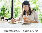 young woman writing in the note ... | Shutterstock . vector #553457272