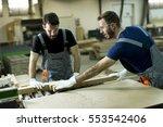 two handsome young men working... | Shutterstock . vector #553542406