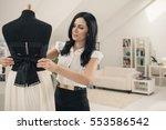 tailor adjusting a dress on a
