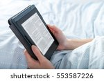 Small photo of Woman reading ebook on tablet reader in bed at home