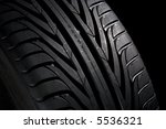 Closeup of a new, black tyre. Black background. - stock photo