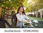 Small photo of Young woman smiling to the camera while sitting with notepad and laptop computer in beautiful city park, Copy space for your text message or informative content.