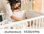 mother putting baby to sleep at ... | Shutterstock . vector #553825996