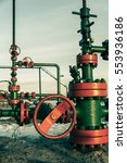Small photo of Group of wellhead. Oilfield with sand ground. Oil and gas concept