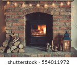 Log burner fireplace with burning logs, handmade wooden toys, lantern and logs around, selective focus; dark vintage style toned photo - stock photo