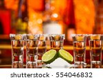 Small photo of two shots of tequila with lime and salt on a wooden table bar on the background of bright lights of the bar