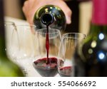 red wine pouring into a wine... | Shutterstock . vector #554066692