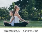 mother and daughter doing yoga... | Shutterstock . vector #554191042