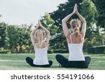 mother and daughter doing yoga... | Shutterstock . vector #554191066