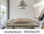 Room with wood dining table, white chairs and industrial lamp