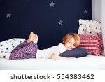 cute kid in pajamas lying in bed | Shutterstock . vector #554383462