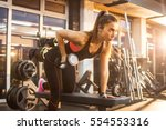 Sportswoman lifting weights in...