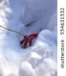 Small photo of Toy man hanging on a rope in the snowy abyss
