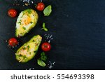 baked avocado with eggs  top... | Shutterstock . vector #554693398