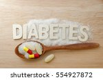 Small photo of Diabetes concept. Alphabet with word DIABETES with sugar,tablet,pills,capsule and wooden spoon on wooden background.