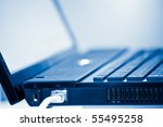 network cable and laptop computer detail with shallow depth of field blue toned - stock photo