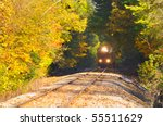 A locomotive parked on an old track in an autumn thicket of woods - stock photo