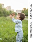 Small photo of One years old caucasian child boy blowing soap bubbles outdoor at sunset - happy carefree childhood