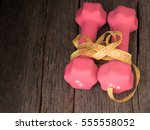 Small photo of Two dumb bells bind by a yellow measuring tape over a wooden table,high angle