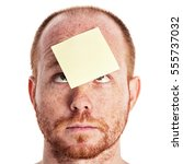Small photo of Adult male with a blank yellow sticky reminder note stuck to his forehead