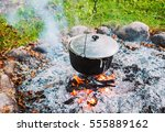 metal pot over a campfire... | Shutterstock . vector #555889162