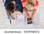 couple using calculator for... | Shutterstock . vector #555948472