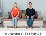 Stock photo portrait of young shy couple sitting on sofa at home 555948475