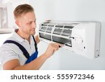 Small photo of Happy Male Technician Repairing Air Conditioner With Screwdriver