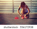 young woman runner tying... | Shutterstock . vector #556172938
